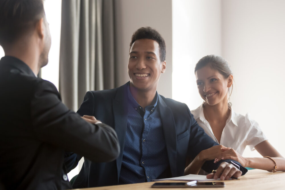 Smiling Diverse Couple Handshaking With Financial Advisor
