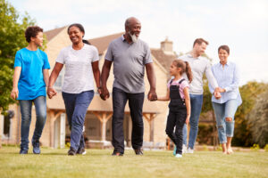 Smiling Multi Generation Mixed Race Family Walking In Garden At Home